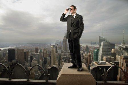 Photo pour Homme d'affaires à l'aide de jumelles sur le toit d'un gratte-ciel - image libre de droit