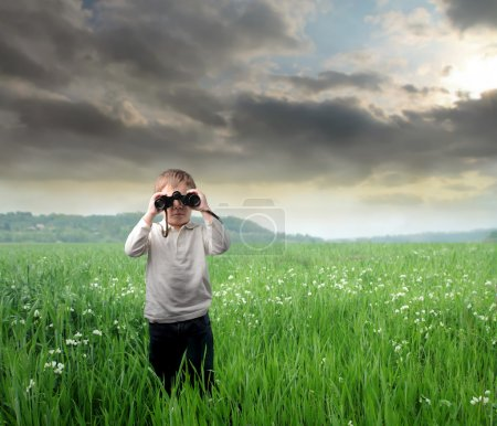 Photo for Child using binoculars on a green meadow - Royalty Free Image