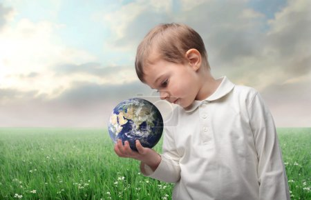 Photo for Child holding the earth with green meadow on the background - Royalty Free Image