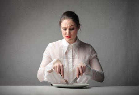 Photo pour Femme avec une expression douteuse à l'aide d'un couteau et d'une fourchette sur un plat - image libre de droit