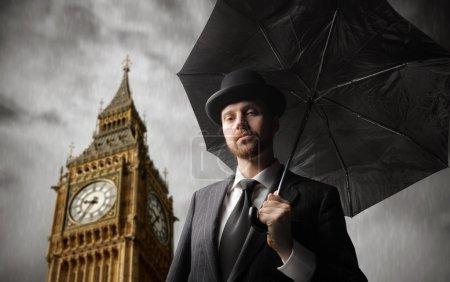 Photo pour Gentleman avec parapluie avec big ben sur le fond - image libre de droit
