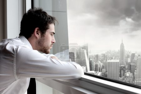 Photo for Tired businessman looking out of the window of an office building - Royalty Free Image