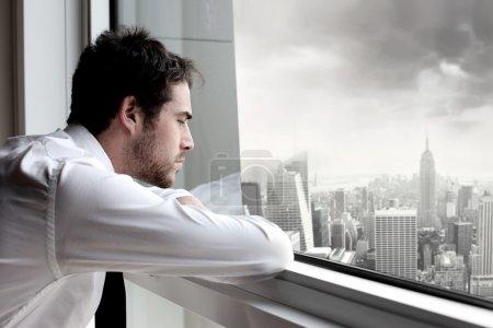 Photo pour Homme d'affaires fatigué regarde par la fenêtre d'un immeuble de bureaux - image libre de droit