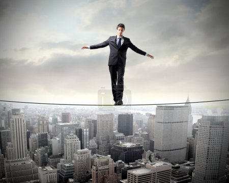Photo for Businessman standing on a rope suspended over a city - Royalty Free Image