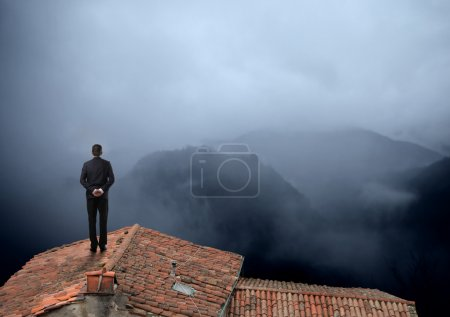 Photo for Businessman looking at a foggy panorama - Royalty Free Image