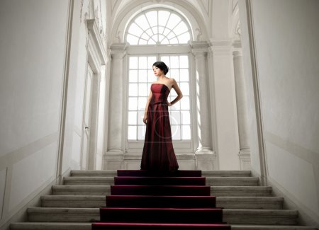 Photo for Beautiful woman in wonderful dress standing on a staircase in a luxury interior - Royalty Free Image