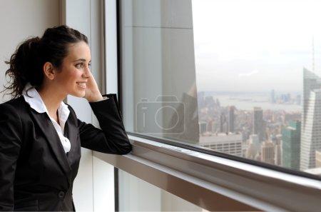 Photo pour Souriante jeune femme regardant par la fenêtre d'un bureau - image libre de droit