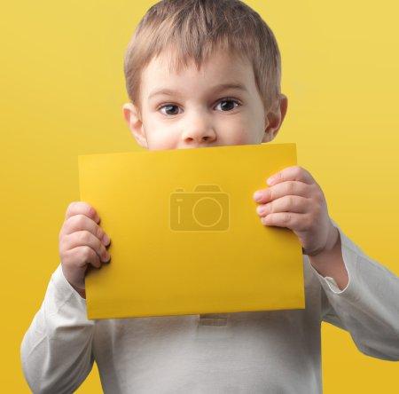 Photo pour Enfant tenant une feuille de papier jaune - image libre de droit