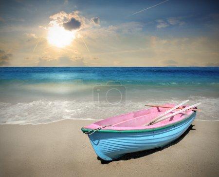 Photo pour Bateau en bois laissé sur le rivage au coucher du soleil - image libre de droit