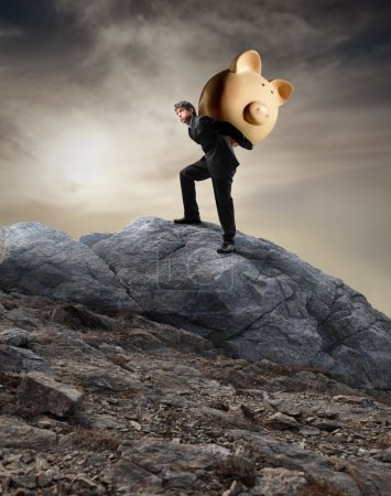 Photo for Businessman carrying a piggy-bank on his shoulders while climbing a rock - Royalty Free Image