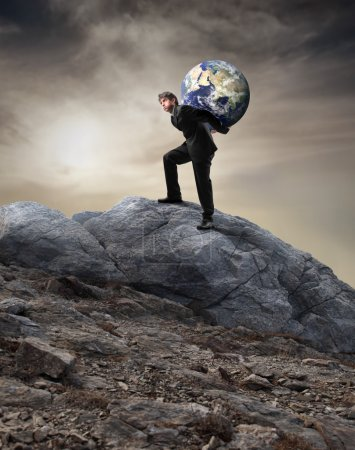 Photo pour Homme d'affaires portant la terre sur ses épaules alors qu'il montait sur un rocher - image libre de droit