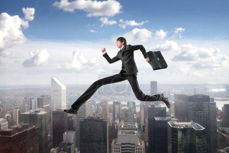 Foto de Empresario con piernas largas por los rascacielos de la ciudad - Imagen libre de derechos