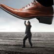Businessman withstanding a giant foot squashing him