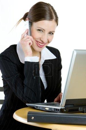 Photo pour Femme d'affaires au téléphone avec un ordinateur portable - image libre de droit