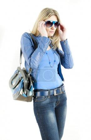 Photo pour Portrait de femme debout portant des vêtements bleus avec sac à main - image libre de droit