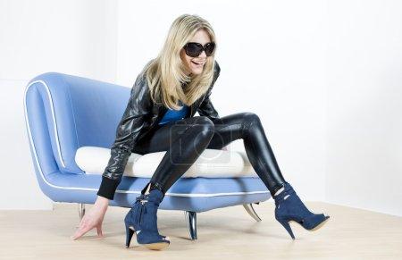 Photo pour Femme portant des chaussures à la mode assis sur le canapé - image libre de droit