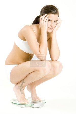Foto de Mujer vestida con ropa interior en la escala de peso - Imagen libre de derechos