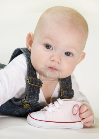 Photo for Portrait of lying down baby girl holding a shoe - Royalty Free Image