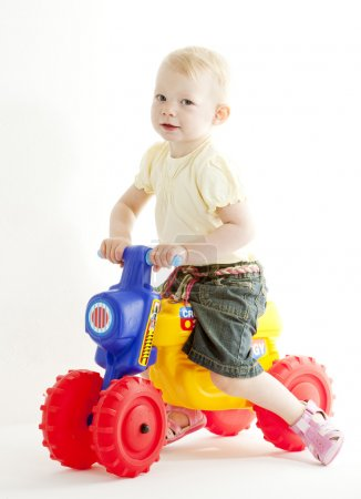 Little girl on toy motorcycle