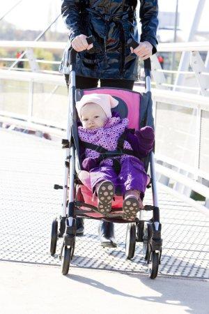 Woman with toddler sitting in pram on walk