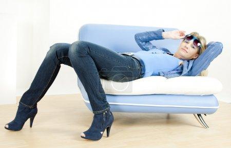 Photo pour Femme portant des vêtements bleus allongés sur le canapé - image libre de droit