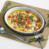 Baked white asparagus with cherry tomatoes on rosemary