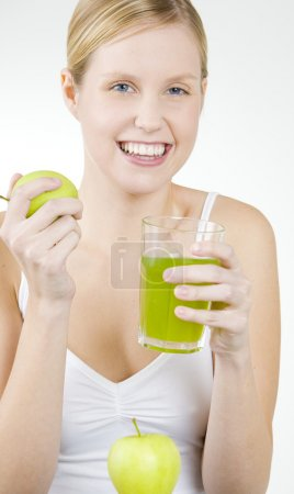 Woman with a glass of juice and apples