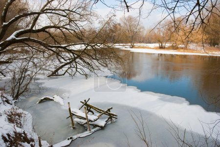 River in winter, coast are covered by snow...