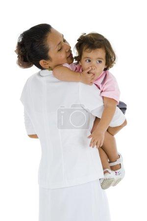 Photo pour Femme qui pourrait être sa mère, une infirmière, nounou ou enseignant détenant une fille douce 2, isolée sur fond blanc - image libre de droit