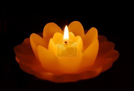 Photo pour Trois bougies orange en forme de fleur sur fond sombre - image libre de droit