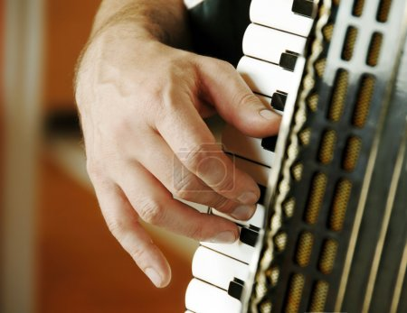 Musician hand playing accordion