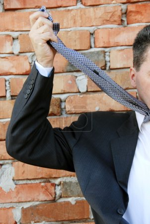 Businessman smothering himself with necktie by bri...
