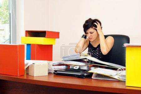 Foto de Mujer estresada en escritorio sobrecargado de trabajo manteniendo su cabeza se desesperó - Imagen libre de derechos