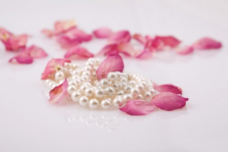 Photo pour Belles perles de perles et pétales de roses rouges - image libre de droit