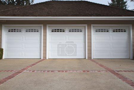 Photo pour Garage ar trois beige avec portes en blanc et allée de brique rouge et brique - image libre de droit