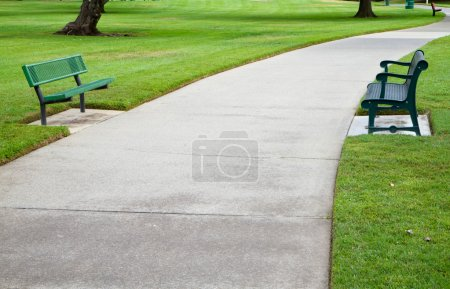 Two green metal benches across a large concrete pa...
