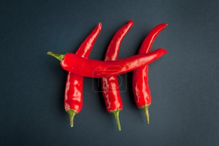 Photo for Four peppers on the black background - Royalty Free Image