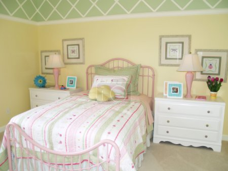 Photo for Bright yellow children's bedroom tastefully decorated with a green diamond border at the ceiling. - Royalty Free Image