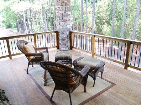 Photo pour Meubles en osier assis sur une terrasse en bois surplombant une forêt de pins - image libre de droit