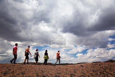 Photo pour Groupe de touristes dans le désert et les nuages de tempête - image libre de droit
