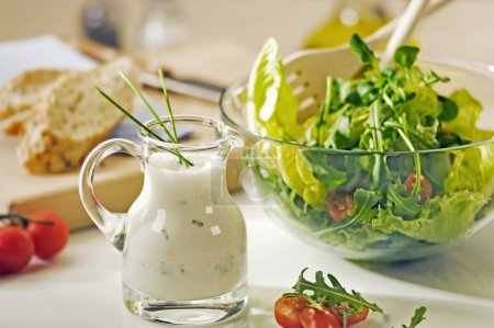Bowl of greens and a jug of salad dressing...