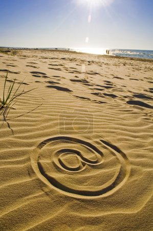 At sign drawn in the sand