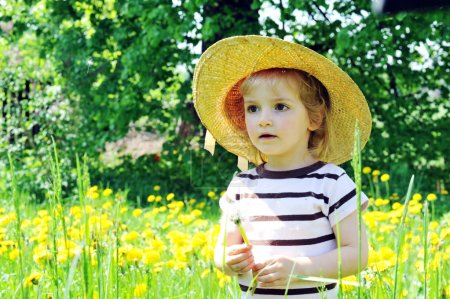 Photo pour Petite fille en chapeau de paille marche sur le champ en fleurs - image libre de droit