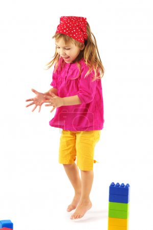 Photo for Jumping happy little girl with colorful bricks on white background. - Royalty Free Image