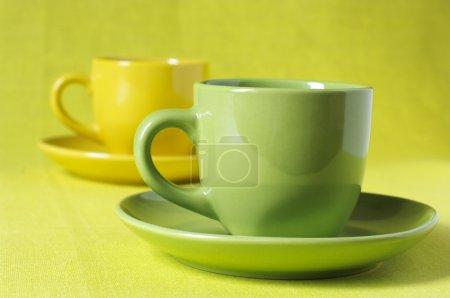Photo pour Café dans des tasses jaunes et verts avec soucoupes sur toile de lin jaune citron. - image libre de droit