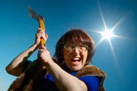 Woman with axe on background blue sky...