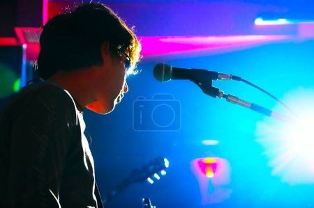 Photo for Music performer on scene in nocturnal club - Royalty Free Image