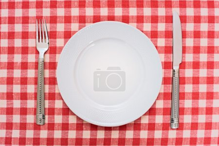 Photo for Empty dinner plate with fork and knife on red and white checked gingham tablecloth - Royalty Free Image