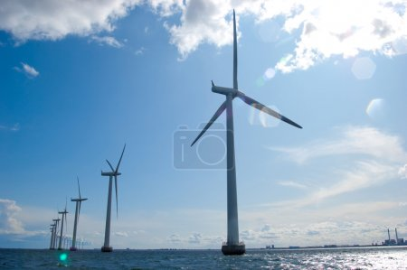Windmills in a row on sunny day with lens flare
