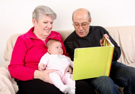 Family reading book to baby